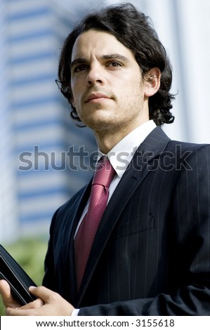 A young businessman standing outside with city building behind (shallow depth of field used)