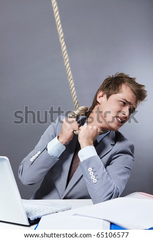 A young businessman tightens the noose on his neck - stock photo