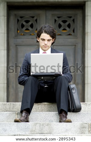 A young businessman using a laptop outside