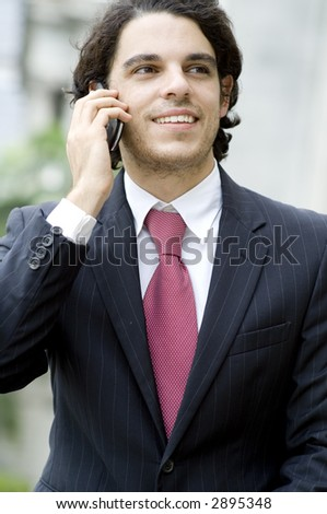 A young businessman using mobile phone outside (shallow depth of field used)