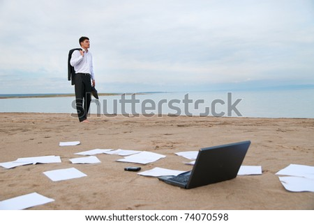 A young businessman walking on the beach. On the sand scattered papers, laptop and mobile phone.