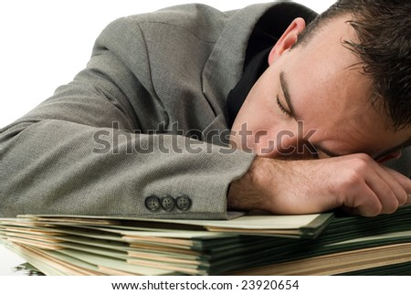 A young businessman who fell asleep on his paperwork - stock photo