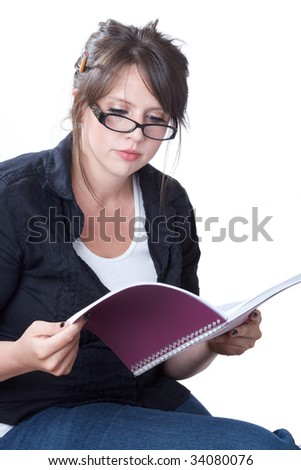 A young businesswoman in casual attire reviews her planner; isolated on a white background. - stock photo