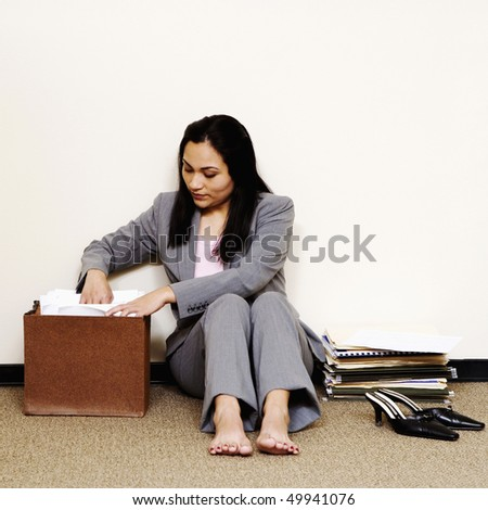 A young businesswoman is sitting on the floor with her shoes off and looking through a file folder. Square shot.