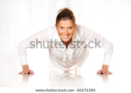 A young businesswoman making pushups and smiling - stock photo