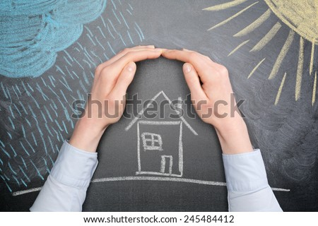 A young businesswoman protects a house from the elements - rain or storm and sun. Blackboard drawing, top view. - stock photo