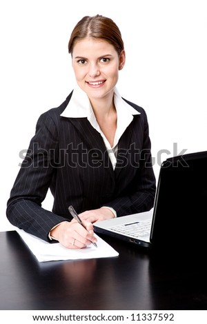 A young businesswoman sat at a desk with laptop computer - stock photo