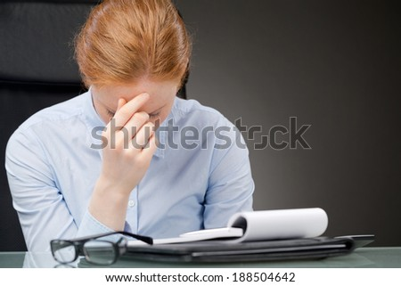 A young businesswoman sitting behind a desk with a notebook and thinking.