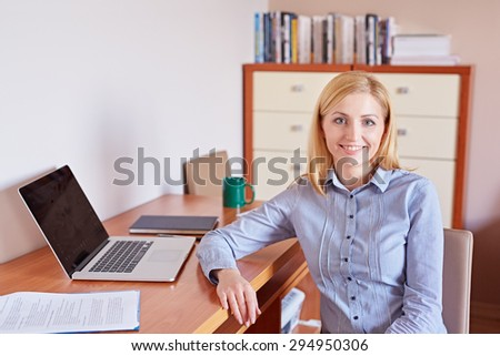 A young businesswoman smiling at the camera while sitting in her office - stock photo