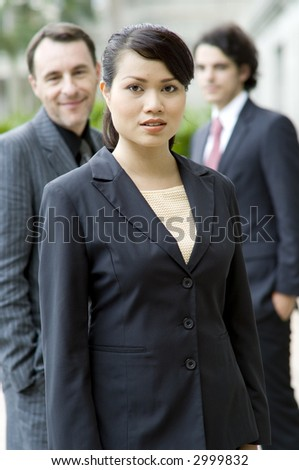 A young businesswoman standing in front of two male colleagues (shallow depth of field used)