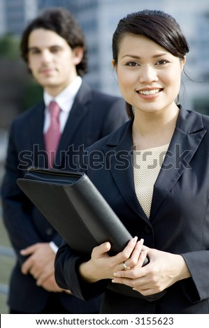 A young businesswoman standing outside with a male colleague standing behind her (shallow depth of field)