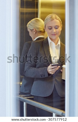 A young businesswoman texting someone in elevator - stock photo