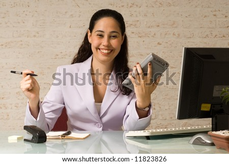 A young businesswoman, with a big smile, holding a pen and calculator at glass desk. - stock photo