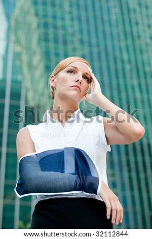 A young businesswoman with injured arm and band-aid standing in the city - stock photo