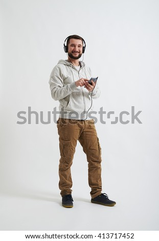A young Caucasian bearded man in casual clothes with headphones on his head is smiling and holding a phone in his hands - stock photo