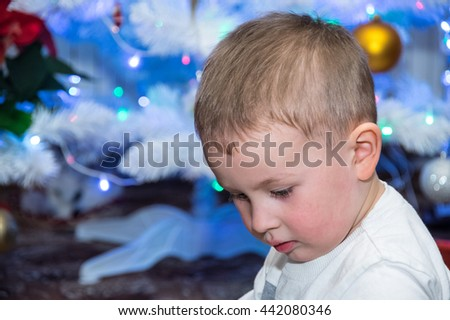 a young caucasian boy at background of xmas tree - stock photo