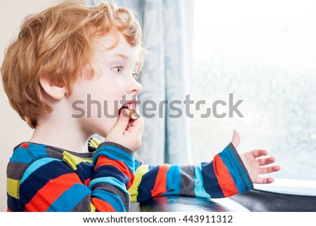 A young caucasian boy eating a chocolate finger in front of a brightly lit window - stock photo