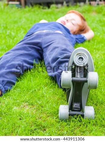 A young caucasian boy laying on grass outside wearing a pair of roller-skates - stock photo