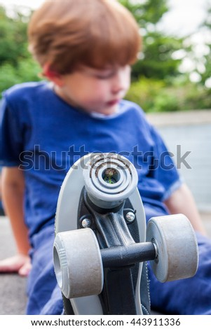 A young caucasian boy looking down in the background with roller-skates he is wearing in focus in the foreground - stock photo