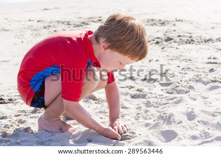 A young caucasian boy playing with the sand on a beach - stock photo