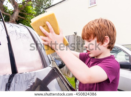 A young caucasian boy using two sponges to wash a car - stock photo