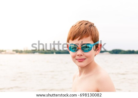 A young caucasian boy wearing swimming goggles looking at the camera with a lake behind him