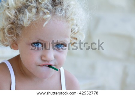 a young caucasian child with a dangerous small object in her mouth - stock photo