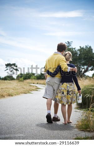 A young caucasian couple taking a walk in a park - stock photo