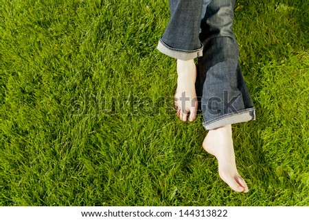 A young Caucasian female feet relaxed over green grass.
