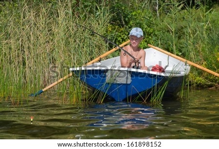 A young caucasian fisherman is fishing from a boat - stock photo