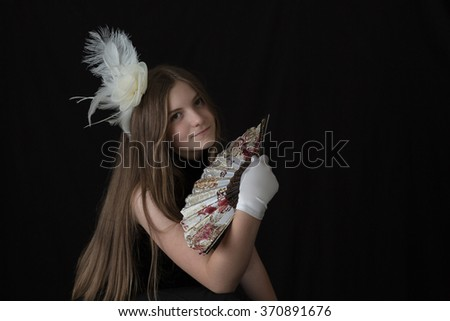 A young caucasian girl dressed in black with a white feather hair pin, white gloves, and a spanish/oriental fan. All with a dramatic black background and lovely natural lighting. Horizontal format. - stock photo