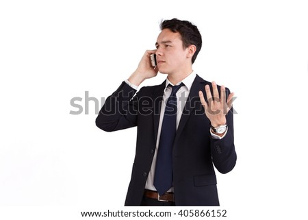 A young caucasian male businessman frowns with raised hand while holding a mobile phone looking away from camera.