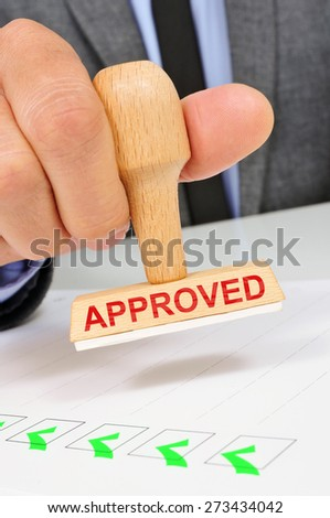 a young caucasian man at his office desk with a rubber stamp with the word approved - stock photo