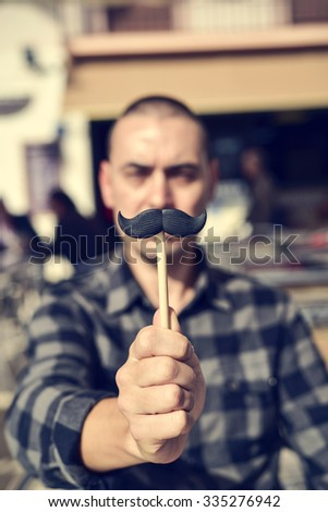 a young caucasian man holding a fake moustache in a stick in front of his face - stock photo