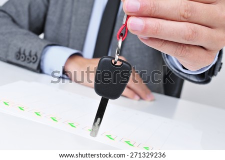 a young caucasian man in a grey suit sitting at his office desk gives a car key to the observer - stock photo
