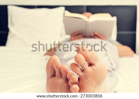 a young caucasian man in pajamas reading a book in bed - stock photo