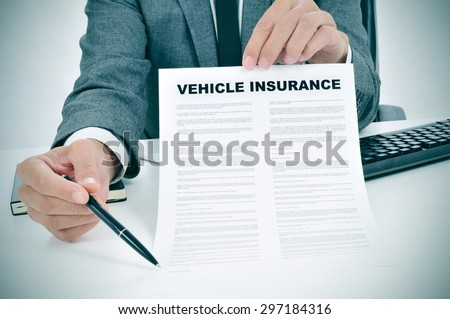 a young caucasian man wearing a gray suit in his office shows a vehicle insurance policy and points with a pen where the policyholder must to sign - stock photo
