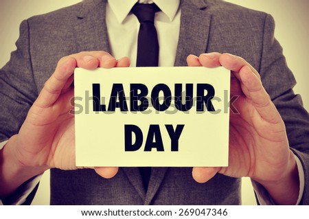 a young caucasian man wearing a gray suit shows a signboard with the text labour day written in it, filtered - stock photo