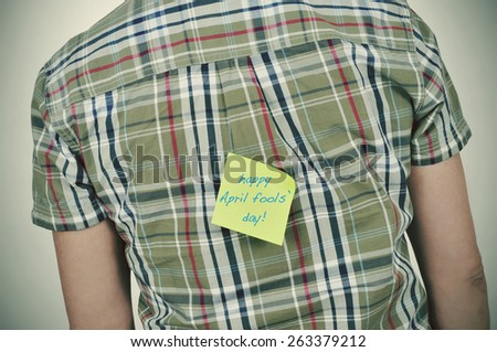 a young caucasian man wearing a plaid patterned shirt with a yellow sticky note attached to his back with the text happy april fools day written in it - stock photo