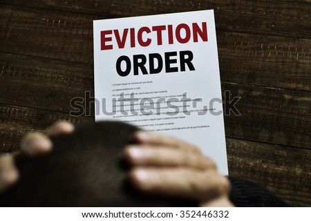 a young caucasian man with his hands in his head concerned because has just received an eviction order - stock photo