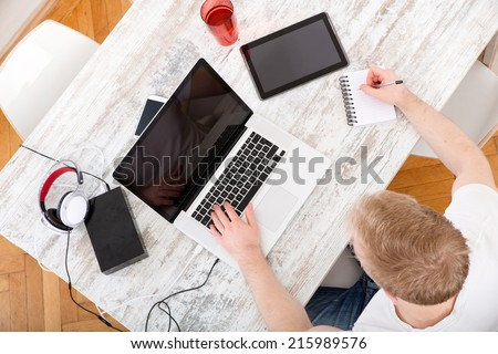 A young caucasian man working in his home office seen from above.  - stock photo