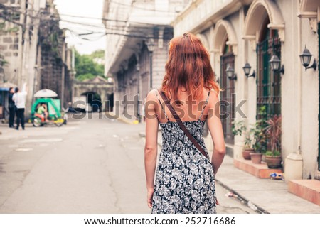 A young caucasian woman is walking in Manila - stock photo