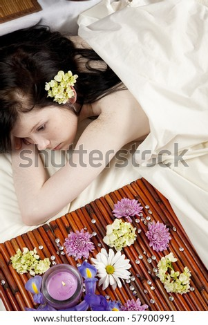 A young Caucasian woman lies on a massage table with a candle and flowers. - stock photo