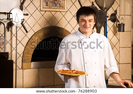 A young chef standing next to oven - indoor