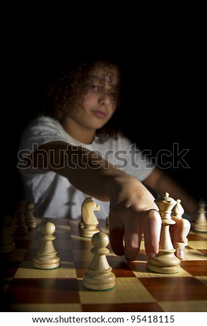 A young chess player moving the Queen - stock photo