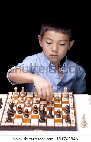 A young chess player starts to make a move on the chess board.