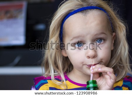 A young child drinking from a bottle with a straw - stock photo