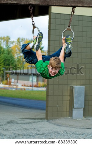 A young child having fun playing on equipment at a playground. - stock photo