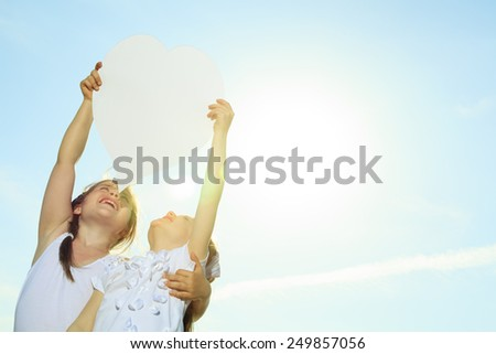 A young child holding heart over the sky