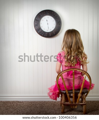 A young child in time out or in trouble, with clock on wall - stock photo